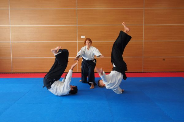 Ключ рекорды. Фото женщина, мастер Айкидо бросает двух мужиков одним махом
