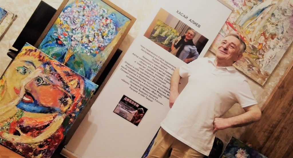 Хасай Алиев на фоне своих картин