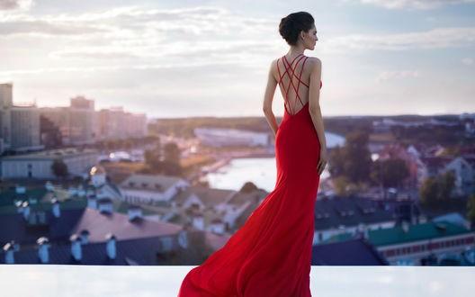 девушка в красном платье на фоне курортного города